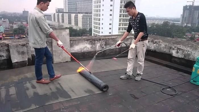 Thợ đang tiến hành khò nóng màng chống thấm cho sân thượng